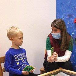 Photo of Riley Lamott working with his speech therapist Lori Jaeger at Ridgeview Pediatric Rehab